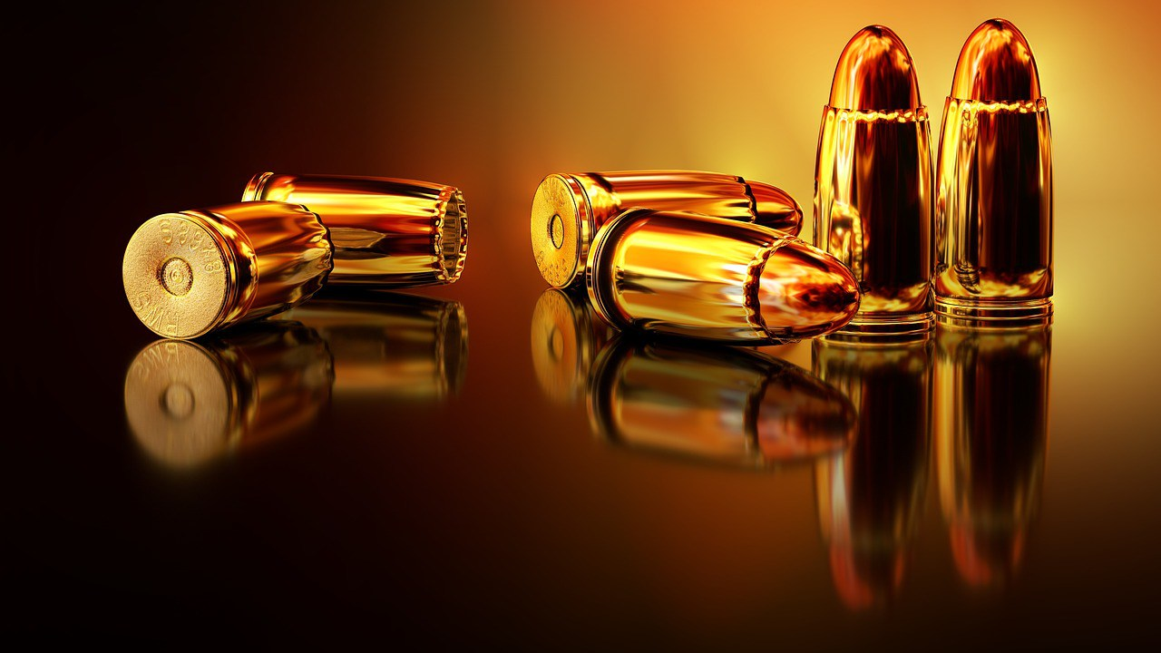 Golden hued image of bullets and casings on a reflective table.