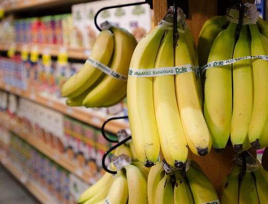 Yellow bananas with an organic label hanging in front of a cereal aisle in a grocery store.