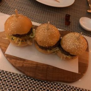 Three Impossible burger sliders on a wooden serving tray.
